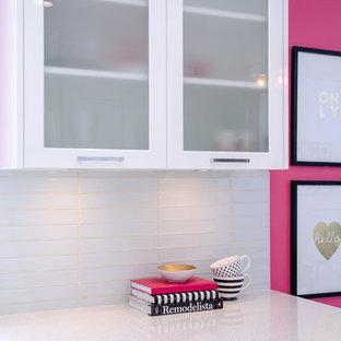 Inspiration pour une cuisine américaine design de taille moyenne avec un placard à porte shaker, des portes de placard blanches, un plan de travail en quartz modifié, une crédence blanche, une crédence en carreau de verre et une péninsule.