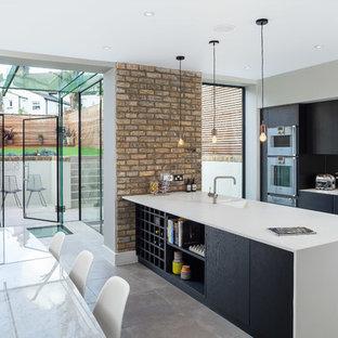 Zweizeilige Moderne Wohnküche mit integriertem Waschbecken, flächenbündigen Schrankfronten, schwarzen Schränken, Küchenrückwand in Metallic, Rückwand aus Spiegelfliesen, Küchengeräten aus Edelstahl, Schieferboden und Halbinsel in London