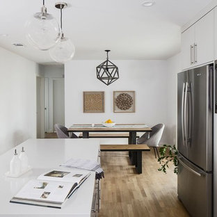 Mid-sized midcentury l-shaped eat-in kitchen in Austin with a farmhouse sink, flat-panel cabinets, grey cabinets, glass benchtops, white splashback, subway tile splashback, stainless steel appliances, light hardwood floors and with island.