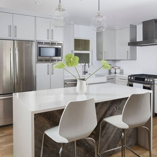 Mid-sized contemporary eat-in kitchen inspiration - Eat-in kitchen - mid-sized contemporary l-shaped medium tone wood floor and brown floor eat-in kitchen idea in Austin with a farmhouse sink, flat-panel cabinets, gray cabinets, white backsplash, subway tile backsplash, stainless steel appliances and an island
