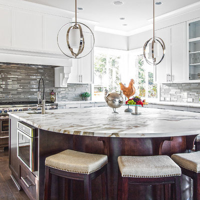 Example of a large transitional u-shaped medium tone wood floor and brown floor kitchen design in Seattle with an undermount sink, shaker cabinets, white cabinets, marble countertops, gray backsplash, glass tile backsplash, paneled appliances, an island and white countertops