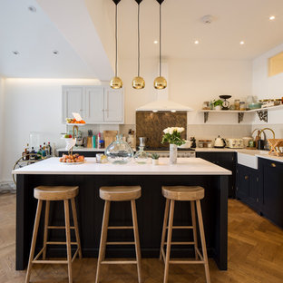 Inspiration for a farmhouse l-shaped kitchen in London with a belfast sink, shaker cabinets, blue cabinets, brown splashback, stainless steel appliances, medium hardwood flooring, an island, brown floors and white worktops.