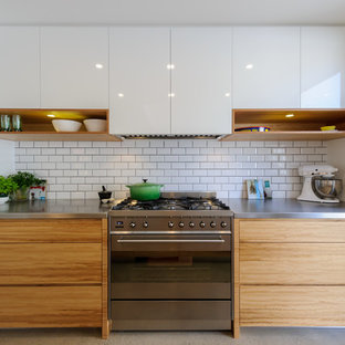 Moderne Küche mit flächenbündigen Schrankfronten, hellbraunen Holzschränken, Edelstahl-Arbeitsplatte, Küchenrückwand in Weiß, Rückwand aus Metrofliesen und Küchengeräten aus Edelstahl in Melbourne