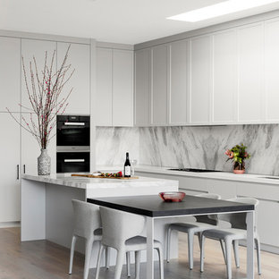 Design ideas for a contemporary l-shaped kitchen in Melbourne with shaker cabinets, white cabinets, grey splashback, stone slab splashback, black appliances, light hardwood floors, with island, beige floor and white benchtop.