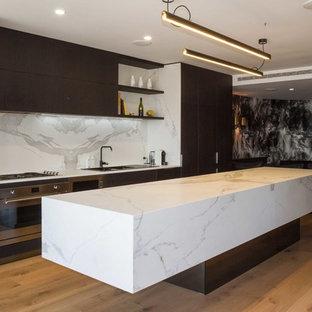 Inspiration för ett mellanstort funkis vit vitt kök, med en nedsänkt diskho, släta luckor, svarta skåp, kaklad bänkskiva, vitt stänkskydd, stänkskydd i porslinskakel, rostfria vitvaror, mellanmörkt trägolv, en köksö och brunt golv