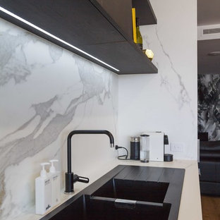 Inspiration for a mid-sized modern galley open plan kitchen in Melbourne with flat-panel cabinets, with island, a drop-in sink, black cabinets, tile benchtops, white splashback, porcelain splashback, stainless steel appliances, medium hardwood floors, brown floor and white benchtop.