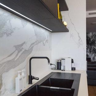 Idéer för att renovera ett mellanstort funkis vit vitt kök, med släta luckor, en köksö, en nedsänkt diskho, svarta skåp, kaklad bänkskiva, vitt stänkskydd, stänkskydd i porslinskakel, rostfria vitvaror, mellanmörkt trägolv och brunt golv