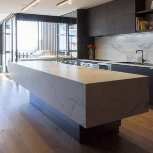 メルボルンの中くらいのモダンスタイルのおしゃれなキッチン (フラットパネル扉のキャビネット、ドロップインシンク、黒いキャビネット、タイルカウンター、白いキッチンパネル、磁器タイルのキッチンパネル、シルバーの調理設備、無垢フローリング、茶色い床、白いキッチンカウンター) の写真