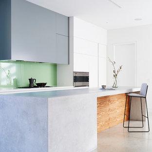 Imagen de cocina comedor minimalista, de tamaño medio, con armarios con paneles lisos, suelo de cemento, una isla, puertas de armario grises, salpicadero gris, fregadero de doble seno, salpicadero de vidrio templado y electrodomésticos de acero inoxidable