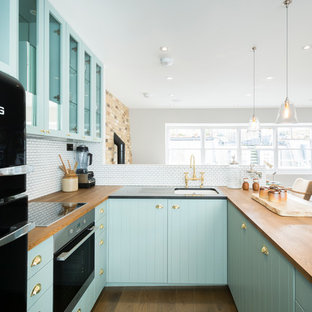Small country u-shaped open plan kitchen in London with glass-front cabinets, blue cabinets, wood worktops, a breakfast bar, a submerged sink, white splashback, black appliances and dark hardwood flooring.