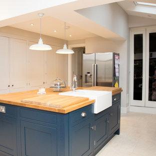 ロンドンの中くらいのモダンスタイルのおしゃれなキッチン (エプロンフロントシンク、シェーカースタイル扉のキャビネット、グレーのキャビネット、木材カウンター、グレーのキッチンパネル、ガラス板のキッチンパネル、黒い調理設備、セラミックタイルの床、ベージュの床、茶色いキッチンカウンター) の写真