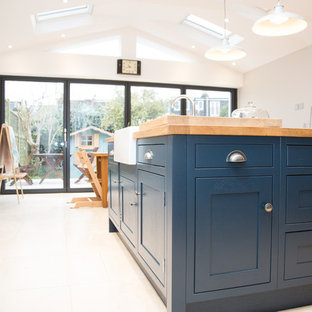 ロンドンの中サイズのモダンスタイルのおしゃれなキッチン (エプロンフロントシンク、シェーカースタイル扉のキャビネット、グレーのキャビネット、木材カウンター、グレーのキッチンパネル、ガラス板のキッチンパネル、黒い調理設備、セラミックタイルの床、ベージュの床、茶色いキッチンカウンター) の写真