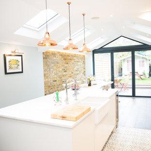 ロンドンの中サイズのエクレクティックスタイルのおしゃれなキッチン (エプロンフロントシンク、フラットパネル扉のキャビネット、白いキャビネット、白いキッチンカウンター、人工大理石カウンター、セラミックタイルの床、マルチカラーの床) の写真