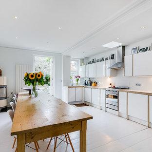 ロンドンの中サイズのカントリー風おしゃれなキッチン (フラットパネル扉のキャビネット、白いキャビネット、木材カウンター、白いキッチンパネル、シルバーの調理設備の、アイランドなし、白い床、白いキッチンカウンター、塗装フローリング) の写真