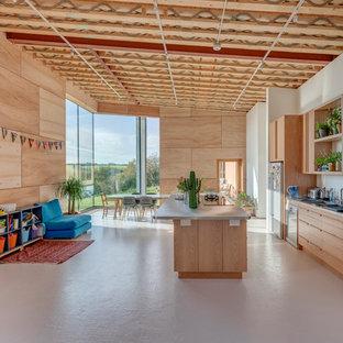 コーンウォールのエクレクティックスタイルのおしゃれなキッチン (フラットパネル扉のキャビネット、淡色木目調キャビネット、シルバーの調理設備、ベージュの床、グレーのキッチンカウンター) の写真