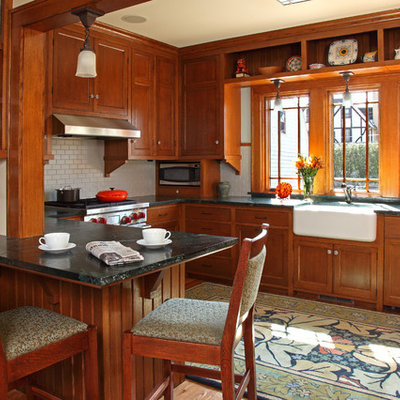 Eat-in kitchen - craftsman u-shaped medium tone wood floor eat-in kitchen idea in Minneapolis with a farmhouse sink, recessed-panel cabinets, medium tone wood cabinets, white backsplash, subway tile backsplash, stainless steel appliances, soapstone countertops and a peninsula