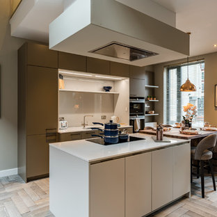 Modern galley kitchen/diner in West Midlands with flat-panel cabinets, grey cabinets, grey splashback, black appliances, light hardwood flooring, an island and beige floors.