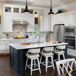 Geräumige Maritime Wohnküche in U-Form mit Unterbauwaschbecken, Schrankfronten mit vertiefter Füllung, weißen Schränken, Onyx-Arbeitsplatte, Küchenrückwand in Weiß, Rückwand aus Stäbchenfliesen, Küchengeräten aus Edelstahl, braunem Holzboden und Kücheninsel in Tampa
