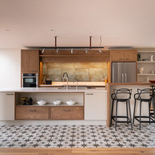 Inspiration for a large contemporary galley kitchen in Kent with a submerged sink, flat-panel cabinets, white cabinets, green splashback, stainless steel appliances, an island, multi-coloured floors and white worktops.