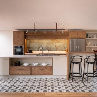 ケントの広いコンテンポラリースタイルのおしゃれなキッチン (アンダーカウンターシンク、フラットパネル扉のキャビネット、白いキャビネット、緑のキッチンパネル、シルバーの調理設備、マルチカラーの床、白いキッチンカウンター) の写真
