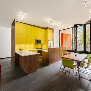 Diseño de cocina en L, contemporánea, abierta, con armarios con paneles lisos, puertas de armario amarillas, salpicadero amarillo y electrodomésticos de acero inoxidable