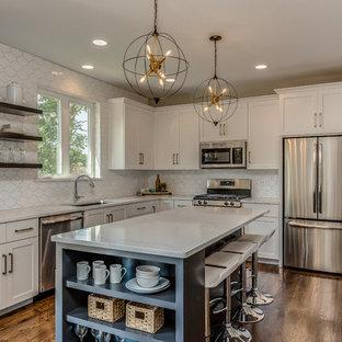 Foto di una cucina minimalista di medie dimensioni con ante bianche, isola, top bianco, lavello a vasca singola, paraspruzzi bianco, elettrodomestici in acciaio inossidabile, parquet scuro, pavimento marrone e ante in stile shaker