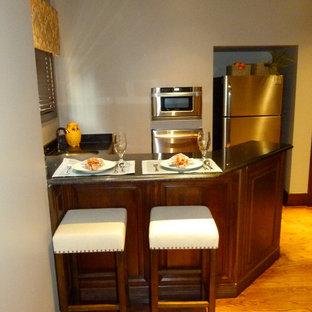 他の地域の小さい地中海スタイルのおしゃれなキッチン (ドロップインシンク、濃色木目調キャビネット、御影石カウンター、シルバーの調理設備の、淡色無垢フローリング、黄色い床、黒いキッチンカウンター) の写真