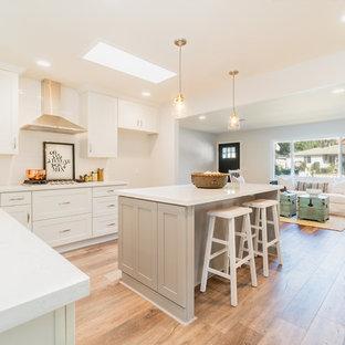 他の地域の地中海スタイルのおしゃれなキッチン (一体型シンク、落し込みパネル扉のキャビネット、白いキャビネット、白いキッチンパネル、塗装フローリング、ベージュの床、白いキッチンカウンター) の写真