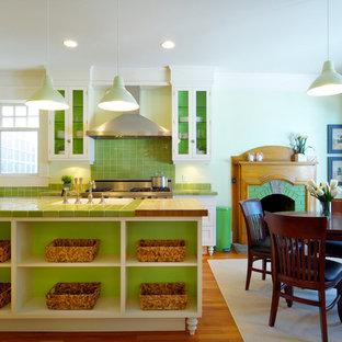 カルガリーのトラディショナルスタイルのおしゃれなダイニングキッチン (シルバーの調理設備の、タイルカウンター、エプロンフロントシンク、ガラス扉のキャビネット、白いキャビネット、緑のキッチンパネル、緑のキッチンカウンター) の写真