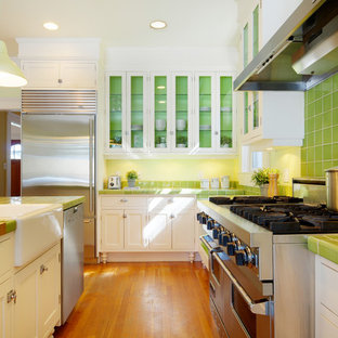 This is an example of a traditional kitchen in Calgary with stainless steel appliances, a farmhouse sink, tile benchtops, glass-front cabinets, white cabinets, green splashback and green benchtop.