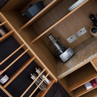ロンドンの広いヴィクトリアン調のおしゃれなキッチン (一体型シンク、落し込みパネル扉のキャビネット、黒いキャビネット、御影石カウンター、ベージュキッチンパネル、ガラス板のキッチンパネル、シルバーの調理設備、ライムストーンの床) の写真