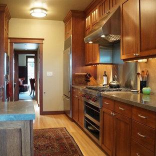 Idee per una cucina stile americano con lavello sottopiano, ante in stile shaker, ante in legno bruno, top in pietra calcarea, paraspruzzi in lastra di pietra e elettrodomestici in acciaio inossidabile
