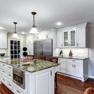 Идея дизайна: п-образная кухня в стиле современная классика с обеденным столом, раковиной в стиле кантри, белыми фасадами, гранитной столешницей, белым фартуком, фартуком из травертина, техникой из нержавеющей стали, пробковым полом, островом и коричневым полом