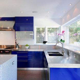 Foto de cocina en L, contemporánea, grande, abierta, con fregadero integrado, armarios con paneles lisos, puertas de armario azules, encimera de cuarzo compacto, salpicadero blanco, electrodomésticos de acero inoxidable, suelo de baldosas de porcelana y una isla