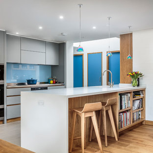 Contemporary galley kitchen in Other with flat-panel cabinets, grey cabinets, blue splashback, glass sheet splashback, black appliances, a breakfast bar, beige floors and white worktops.