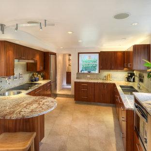 シアトルの大きいトロピカルスタイルのおしゃれなキッチン (アンダーカウンターシンク、フラットパネル扉のキャビネット、中間色木目調キャビネット、御影石カウンター、シルバーの調理設備の、磁器タイルの床、グレーのキッチンパネル、セラミックタイルのキッチンパネル、ベージュの床、マルチカラーのキッチンカウンター) の写真