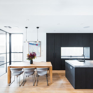 Inspiration for a mid-sized contemporary galley open plan kitchen in Melbourne with black cabinets, quartz benchtops, window splashback, black appliances, with island, grey benchtop, an undermount sink, flat-panel cabinets, medium hardwood floors and brown floor.