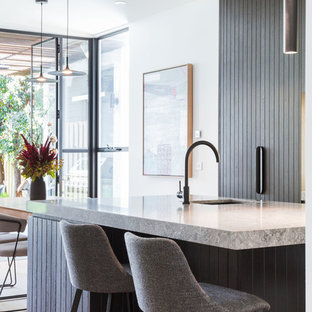 Inspiration for a mid-sized contemporary galley open plan kitchen in Melbourne with black cabinets, quartz benchtops, light hardwood floors, with island, grey benchtop, an undermount sink, flat-panel cabinets and beige floor.