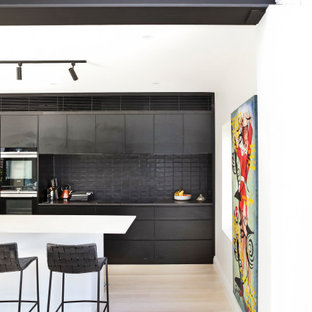 Photo of a contemporary galley kitchen in Sydney with flat-panel cabinets, black cabinets, black splashback, stainless steel appliances, light hardwood floors, with island, beige floor and black benchtop.
