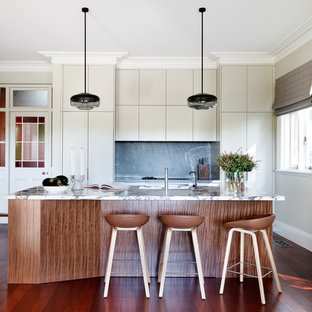 Eclectic galley eat-in kitchen in Sydney with an undermount sink, flat-panel cabinets, marble benchtops, grey splashback, stone slab splashback, stainless steel appliances, medium hardwood floors, with island, brown floor, multi-coloured benchtop and beige cabinets.