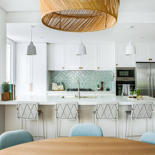 This is an example of a beach style eat-in kitchen in Wollongong with shaker cabinets, white cabinets, green splashback, stainless steel appliances, medium hardwood floors, with island and white benchtop.