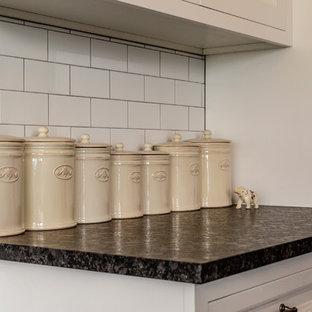 シアトルのヴィクトリアン調のおしゃれなキッチン (ドロップインシンク、落し込みパネル扉のキャビネット、白いキャビネット、御影石カウンター、白いキッチンパネル、セラミックタイルのキッチンパネル、シルバーの調理設備の、スレートの床、グレーの床、黒いキッチンカウンター) の写真