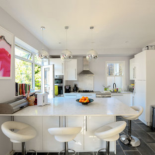 Inspiration for a medium sized contemporary l-shaped kitchen in London with a submerged sink, flat-panel cabinets, white cabinets, white splashback, stainless steel appliances, an island, black floors and white worktops.