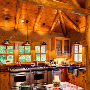 Mountain style dark wood floor and brown floor kitchen photo in Milwaukee with a farmhouse sink, medium tone wood cabinets, window backsplash, stainless steel appliances and an island