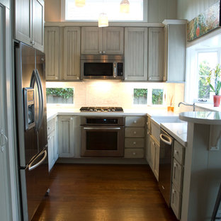 Photo of a small traditional u-shaped eat-in kitchen in San Francisco with a farmhouse sink, louvered cabinets, grey cabinets, quartz benchtops, white splashback, porcelain splashback, stainless steel appliances, medium hardwood floors, no island and brown floor.