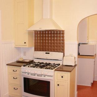 Esempio di una cucina tradizionale di medie dimensioni con ante gialle, elettrodomestici bianchi, lavello da incasso, ante con riquadro incassato, paraspruzzi a effetto metallico, paraspruzzi con piastrelle di metallo e nessuna isola