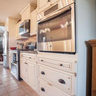 ボストンの中サイズのトランジショナルスタイルのおしゃれなキッチン (ダブルシンク、レイズドパネル扉のキャビネット、ヴィンテージ仕上げキャビネット、御影石カウンター、ベージュキッチンパネル、レンガのキッチンパネル、シルバーの調理設備の、セラミックタイルの床、ベージュの床) の写真