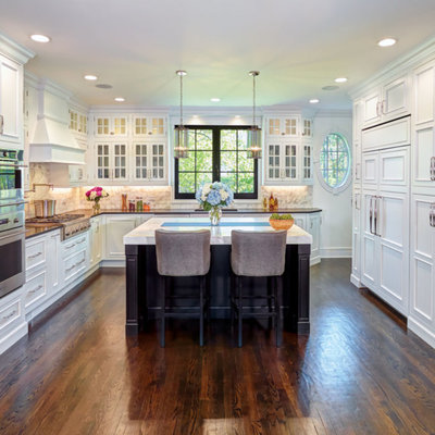 Example of a transitional u-shaped dark wood floor and brown floor kitchen design in Detroit with an undermount sink, recessed-panel cabinets, white cabinets, white backsplash, stainless steel appliances, an island and white countertops