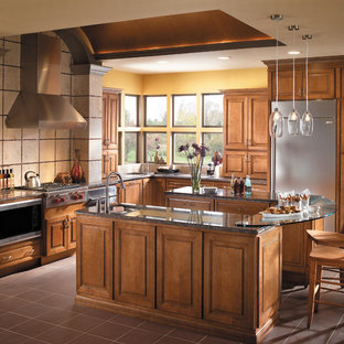 Photo of a large transitional l-shaped open plan kitchen in Other with raised-panel cabinets, medium wood cabinets, glass benchtops, stainless steel appliances, with island, an undermount sink, beige splashback, stone tile splashback, ceramic floors and brown floor.