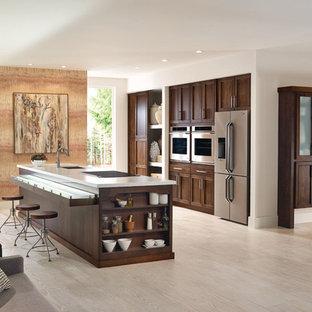 Offene, Einzeilige, Große Klassische Küche mit Kücheninsel, Schrankfronten mit vertiefter Füllung, hellbraunen Holzschränken, Küchengeräten aus Edelstahl, hellem Holzboden, Unterbauwaschbecken und beigem Boden in Sonstige